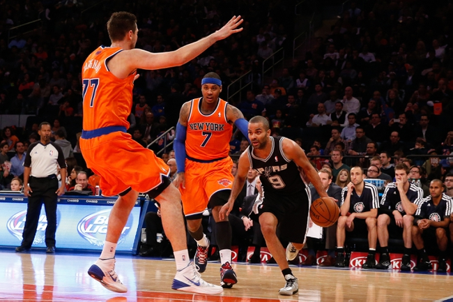 Nov 10, 2013; New York, NY, USA;  San Antonio Spurs point guard Tony Parker (9) drives past New York Knicks small forward Carmelo Anthony (7) and power forward Andrea Bargnani (77) during the third quarter at Madison Square Garden. Spurs won 120-89.  Mandatory Credit: Anthony Gruppuso-USA TODAY Sports