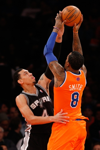 Nov 10, 2013; New York, NY, USA;  New York Knicks shooting guard J.R. Smith (8) and San Antonio Spurs shooting guard Danny Green (4) battle during the third quarter at Madison Square Garden. Spurs won 120-89.  Mandatory Credit: Anthony Gruppuso-USA TODAY Sports
