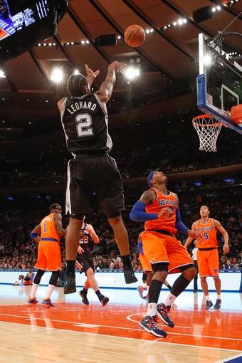 Nov 10, 2013; New York, NY, USA;  San Antonio Spurs small forward Kawhi Leonard (2) shoots over New York Knicks small forward Carmelo Anthony (7) during the fourth quarter at Madison Square Garden. Spurs won 120-89.  Mandatory Credit: Anthony Gruppuso-USA TODAY Sports