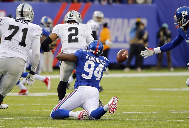 Nov 10, 2013; East Rutherford, NJ, USA;  New York Giants defensive end Mathias Kiwanuka (94) strips Oakland Raiders quarterback Terrelle Pryor (2) late in second half at MetLife Stadium. New York Giants defeat the Oakland Raiders 24-20. Mandatory Credit: Jim O'Connor-USA TODAY Sports