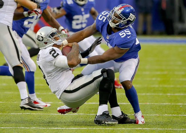 Nov 10, 2013; East Rutherford, NJ, USA;  New York Giants outside linebacker Keith Rivers (55) sacks Oakland Raiders quarterback Terrelle Pryor (2) during the second half at MetLife Stadium. New York Giants defeat the Oakland Raiders 24-20. Mandatory Credit: Jim O'Connor-USA TODAY Sports