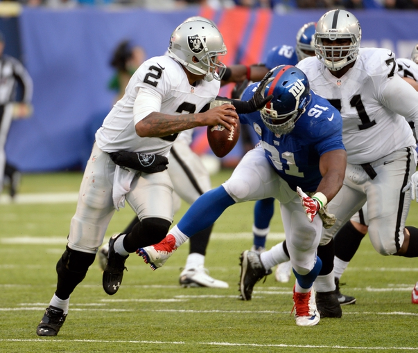 Nov 10, 2013; East Rutherford, NJ, USA; Oakland Raiders quarterback Terrelle Pryor (2) scrambles away from New York Giants defensive end Justin Tuck (91) during the during the second half at MetLife Stadium. Mandatory Credit: Robert Deutsch-USA TODAY Sports