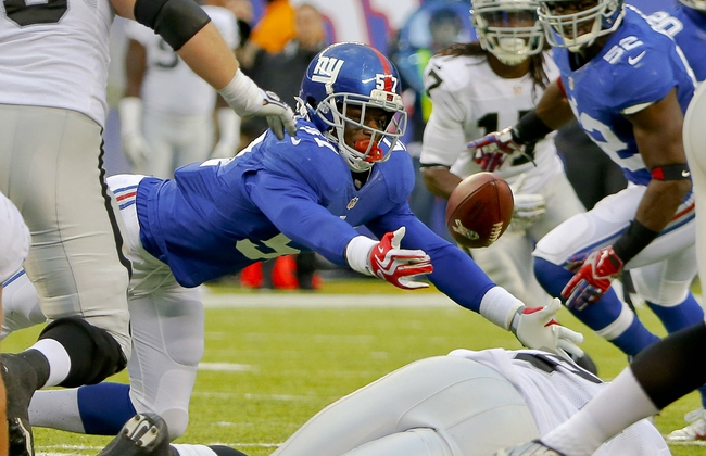 Nov 10, 2013; East Rutherford, NJ, USA;  New York Giants outside linebacker Jacquian Williams (57) dives for deflected pass during the second half against the Oakland Raiders at MetLife Stadium. New York Giants defeat the Oakland Raiders 24-20. Mandatory Credit: Jim O'Connor-USA TODAY Sports
