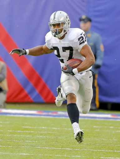 Nov 10, 2013; East Rutherford, NJ, USA;  Oakland Raiders running back Rashad Jennings (27) turns up field after third quarter reception against the New York Giants at MetLife Stadium. New York Giants defeat the Oakland Raiders 24-20. Mandatory Credit: Jim O'Connor-USA TODAY Sports