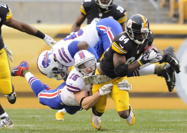 Nov 10, 2013; Pittsburgh, PA, USA; Pittsburgh Steelers wide receiver Antonio Brown (84) is tackled by Buffalo Bills wide receiver Chris Hogan (15) and outside linebacker Arthur Moats (52) on a punt return during the third quarter of a game at Heinz Field. Mandatory Credit: Mark Konezny-USA TODAY Sports