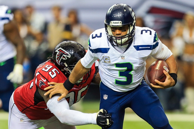Nov 10, 2013; Atlanta, GA, USA; Seattle Seahawks quarterback Russell Wilson (3) stiff arms Atlanta Falcons defensive tackle Jonathan Babineaux (95) as he scrambles away from pressure in the second half at the Georgia Dome. The Seahawks won 33-10. Mandatory Credit: Daniel Shirey-USA TODAY Sports