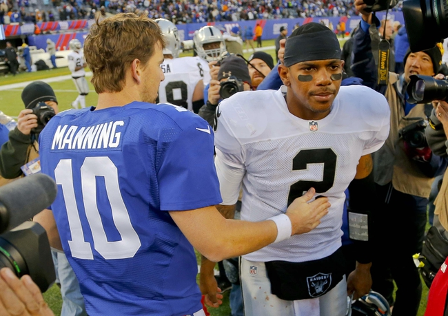 Nov 10, 2013; East Rutherford, NJ, USA;  New York Giants quarterback Eli Manning (10) and Oakland Raiders quarterback Terrelle Pryor (2) after the game at MetLife Stadium. New York Giants defeat the Oakland Raiders 24-20. Mandatory Credit: Jim O'Connor-USA TODAY Sports