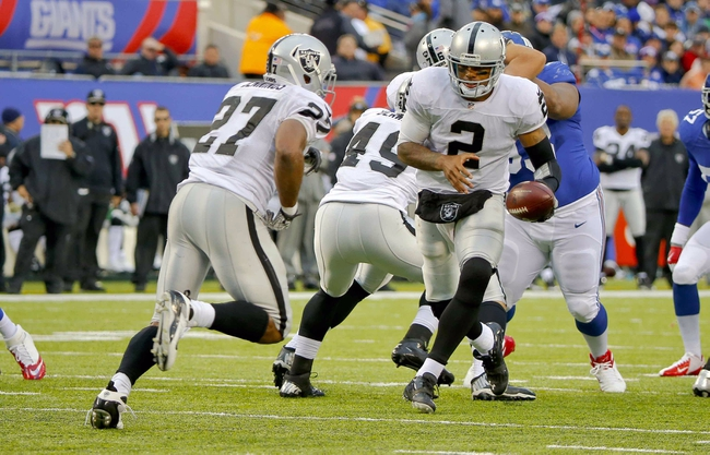 Nov 10, 2013; East Rutherford, NJ, USA;  Oakland Raiders quarterback Terrelle Pryor (2) hands off to running back Rashad Jennings (27) during the second half against the New York Giants at MetLife Stadium. New York Giants defeat the Oakland Raiders 24-20. Mandatory Credit: Jim O'Connor-USA TODAY Sports