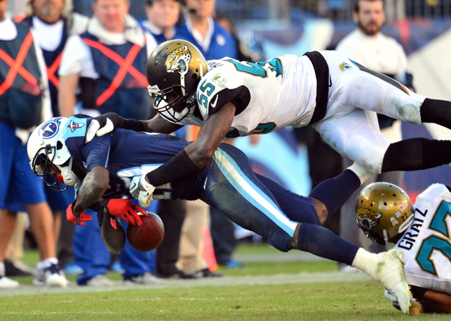 Nov 10, 2013; Nashville, TN, USA; Tennessee Titans wide receiver Kendall Wright (13) is tackled by Jacksonville Jaguars linebacker Geno Hayes (55) during the second half at LP Field. The Jaguars beat the Titans 29-27. Mandatory Credit: Don McPeak-USA TODAY Sports