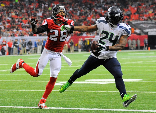 Nov 10, 2013; Atlanta, GA, USA; Seattle Seahawks running back Marshawn Lynch (24) scores a touchdown past Atlanta Falcons safety Thomas DeCoud (28) during the second half at the Georgia Dome. The Seahawks defeated the Falcons 33-10. Mandatory Credit: Dale Zanine-USA TODAY Sports