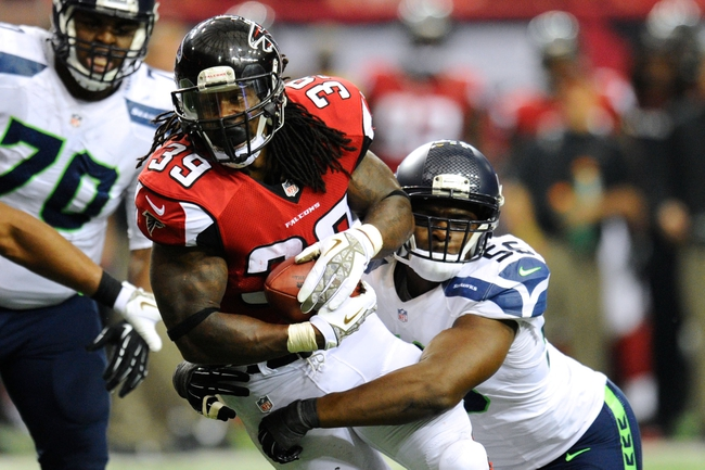 Nov 10, 2013; Atlanta, GA, USA; Atlanta Falcons running back Steven Jackson (39) is tackled by Seattle Seahawks defensive end Cliff Avril (56) during the second half at the Georgia Dome. The Seahawks defeated the Falcons 33-10. Mandatory Credit: Dale Zanine-USA TODAY Sports