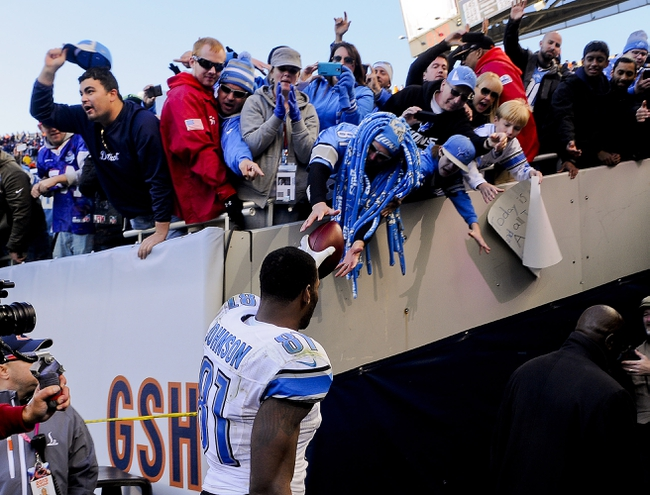 Nov 10, 2013; Chicago, IL, USA;  Detroit Lions wide receiver Calvin Johnson (81) gives the ball to a fan after the Lions beat the Bears 21-19 at Soldier Field. Mandatory Credit: Matt Marton-USA TODAY Sports