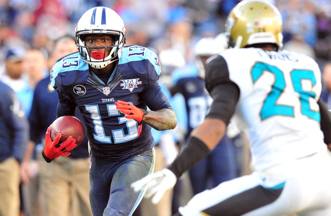 Nov 10, 2013; Nashville, TN, USA; Tennessee Titans wide receiver Kendall Wright (13) carries the ball after a reception against Jacksonville Jaguars safety Josh Evans (26) during the second half at LP Field. The Jaguars beat the Titans 29-27. Mandatory Credit: Don McPeak-USA TODAY Sports