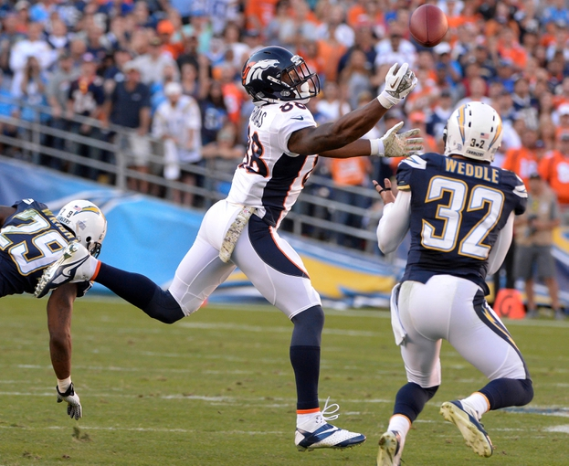 Nov 10, 2013; San Diego, CA, USA;  Denver Broncos wide receiver Demaryius Thomas (88) and San Diego Chargers free safety Eric Weddle (32) battle for a pass during the third quarter at Qualcomm Stadium. Mandatory Credit: Robert Hanashiro-USA TODAY Sports