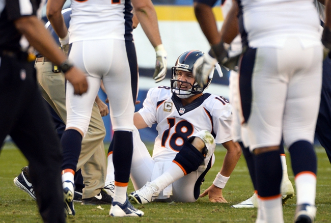 Nov 10, 2013; San Diego, CA, USA;  Denver Broncos quarterback Peyton Manning (18) sits on the turf after injuring his leg during a pass play in the closing minutes of the Broncos win over the San Diego Chargers at Qualcomm Stadium. Manning did not leave the game. Mandatory Credit: Robert Hanashiro-USA TODAY Sports