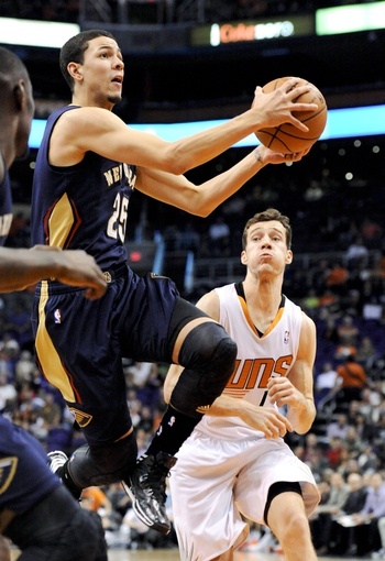 Nov 10, 2013; Phoenix, AZ, USA; New Orleans shooting guard Austin Rivers (25) shoots the ball under pressure from Phoenix Suns point guard Goran Dragic (1) during the fourth quarter at US Airways Center. The Suns beat the Pelicans 101-94. Mandatory Credit: Casey Sapio-USA TODAY Sports
