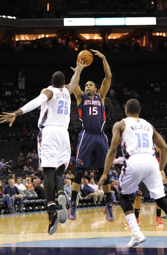 Nov 11, 2013; Charlotte, NC, USA; Atlanta Hawks center forward Al Horford (15) shoots the ball as Charlotte Bobcats center Al Jefferson (25) and guard Kemba walker (15) defend at Time Warner Cable Arena. Mandatory Credit: Sam Sharpe-USA TODAY Sports