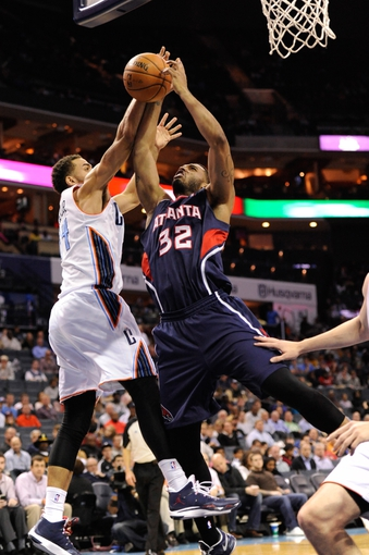 Nov 11, 2013; Charlotte, NC, USA; Atlanta Hawks forward Mike Scott (32) drives to the basket as he is defended by Charlotte Bobcats forward Jeffery Taylor (44) during the game at Time Warner Cable Arena. Mandatory Credit: Sam Sharpe-USA TODAY Sports