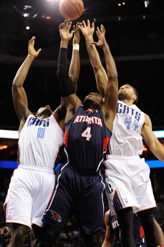 Nov 11, 2013; Charlotte, NC, USA; Charlotte Bobcats forward center Bismack Biyombo (0) (right) Atlanta Hawks forward Paul Millsap (4) (middle) and Charlotte Bobcats guard Jeffery Taylor (right) fight for a rebound during the game at Time Warner Cable Arena. Mandatory Credit: Sam Sharpe-USA TODAY Sports