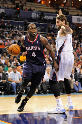 Nov 11, 2013; Charlotte, NC, USA; Atlanta Hawks forward Paul Millsap (4) is defended by Charlotte Bobcats forward Josh McRoberts (11) during the game at Time Warner Cable Arena. Mandatory Credit: Sam Sharpe-USA TODAY Sports