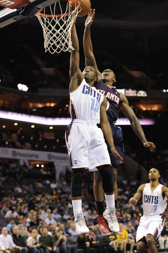 Nov 11, 2013; Charlotte, NC, USA; Charlotte Bobcats guard Kemba Walker (15) shoots the ball as Atlanta Hawks guard Jeff Teague (0) defends during  the third quarter at Time Warner Cable Arena. The Hawks won 103-94. Mandatory Credit: Sam Sharpe-USA TODAY Sports
