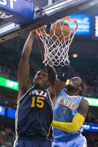 Nov 11, 2013; Salt Lake City, UT, USA; Utah Jazz power forward Derrick Favors (15) shoots the ball as Denver Nuggets power forward J.J. Hickson (7) defends during the second half at EnergySolutions Arena. Denver won 100-81. Mandatory Credit: Russ Isabella-USA TODAY Sports