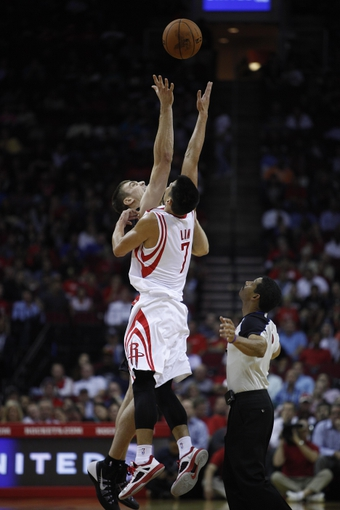 Nov 11, 2013; Houston, TX, USA; Houston Rockets point guard Jeremy Lin (7) and Toronto Raptors power forward Tyler Hansbrough (50) battle for the ball during the third quarter at Toyota Center. The Rockets won 110-104. Mandatory Credit: Andrew Richardson-USA TODAY Sports
