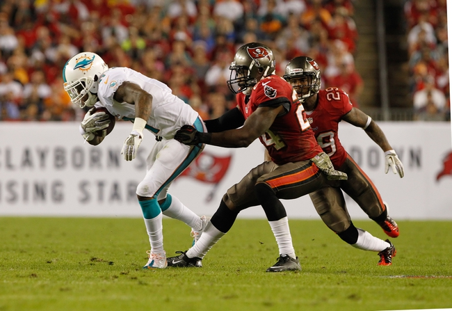 Nov 11, 2013; Tampa, FL, USA; Tampa Bay Buccaneers cornerback Darrelle Revis (24) tackles Miami Dolphins wide receiver Mike Wallace (11) during the second half at Raymond James Stadium. Mandatory Credit: Kim Klement-USA TODAY Sports