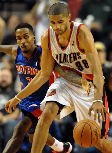Nov 11, 2013; Portland, OR, USA; Detroit Pistons point guard Brandon Jennings (7) reaches in on Portland Trail Blazers small forward Nicolas Batum (88) during the fourth quarter of the game at Moda Center. The Blazers won the game 109-103. Mandatory Credit: Steve Dykes - USA TODAY Sports