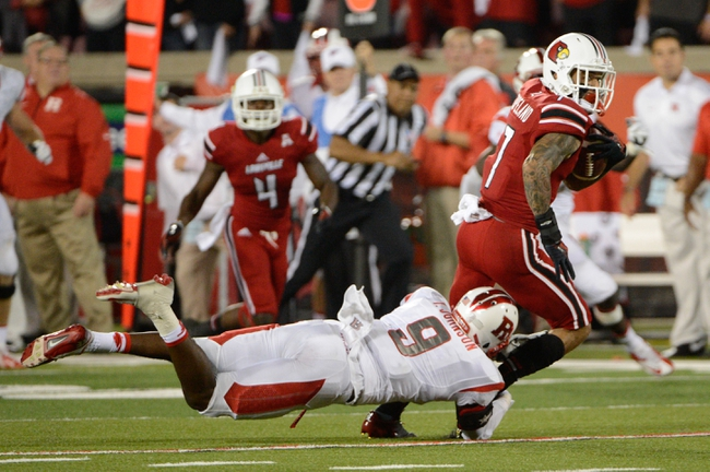 Oct 10, 2013; Louisville, KY, USA; Louisville Cardinals wide receiver Damian Copeland (7) tries to avoid the tackle of Rutgers Scarlet Knights defensive back Tejay Johnson (9) at Papa John's Cardinal Stadium. Mandatory Credit: Jamie Rhodes-USA TODAY Sports
