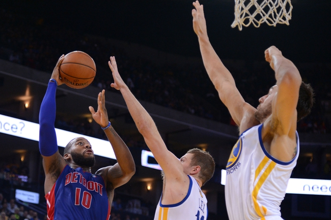 November 12, 2013; Oakland, CA, USA; Detroit Pistons power forward Greg Monroe (10, left) shoots the ball against Golden State Warriors power forward David Lee (10, center) and center Andrew Bogut (12, right) during the second quarter at Oracle Arena. Mandatory Credit: Kyle Terada-USA TODAY Sports