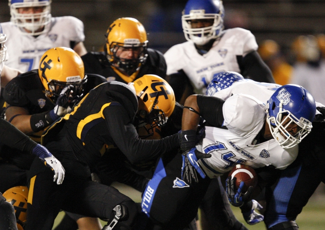 Nov 12, 2013; Toledo, OH, USA; Buffalo Bulls running back Anthone Taylor (14) gets tackled by Toledo Rockets defenders during the fourth quarter at Glass Bowl. The Rockets beat the Bulls 51-41. Mandatory Credit: Raj Mehta-USA TODAY Sports
