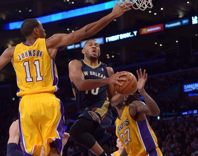 Nov 12, 2013; Los Angeles, CA, USA; New Orleans Pelicans guard Eric Gordon (10) is defended by Los Angeles Lakers forward Wesley Johnson (11) and forward Jordan Hill (27) at Staples Center. The Lakers defeated the Pelicans 116-95. Mandatory Credit: Kirby Lee-USA TODAY Sports