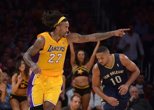 Nov 12, 2013; Los Angeles, CA, USA; Los Angeles Lakers forward Jordan Hill (27) celebrates as New Orleans Pelicans guard Eric Gordon (10) watches at Staples Center. The Lakers defeated the Pelicans 116-95. Mandatory Credit: Kirby Lee-USA TODAY Sports