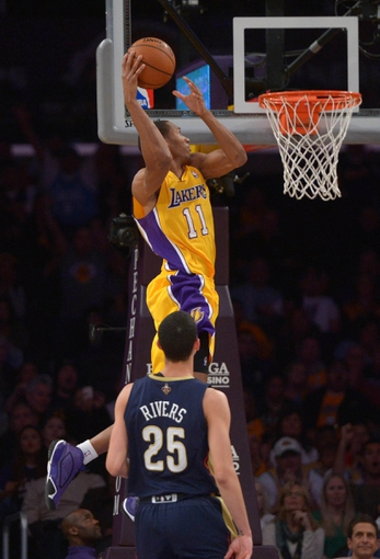 Nov 12, 2013; Los Angeles, CA, USA; Los Angeles Lakers foward Wesley Johnson (11) attempts a dunk as New Orleans Pelicans guard Austin Rivers (25) watches at Staples Center. The Lakers defeated the Pelicans 116-95. Mandatory Credit: Kirby Lee-USA TODAY Sports
