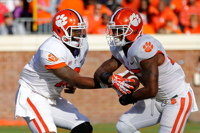 Nov 2, 2013; Charlottesville, VA, USA; Clemson Tigers quarterback Tajh Boyd (10) hands the ball off to Tigers running back Roderick McDowell (25) against the Virginia Cavaliers at Scott Stadium. Mandatory Credit: Geoff Burke-USA TODAY Sports