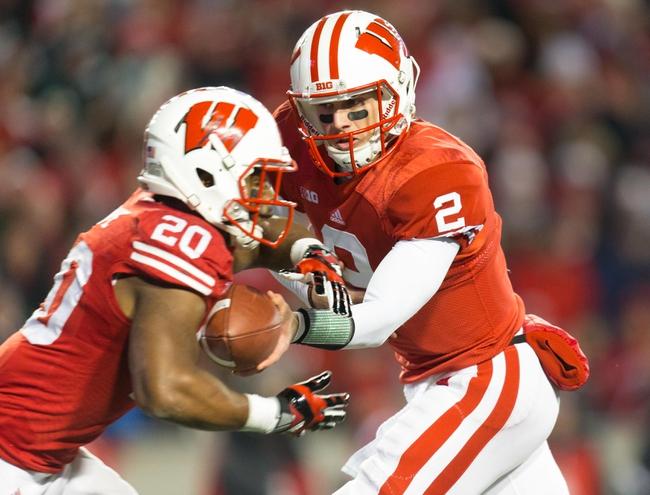Nov 9, 2013; Madison, WI, USA; Wisconsin Badgers quarterback Joel Stave (2) hands the football to running back James White (20) during the game against the Brigham Young Cougars at Camp Randall Stadium. Wisconsin won 27-17.  Mandatory Credit: Jeff Hanisch-USA TODAY Sports