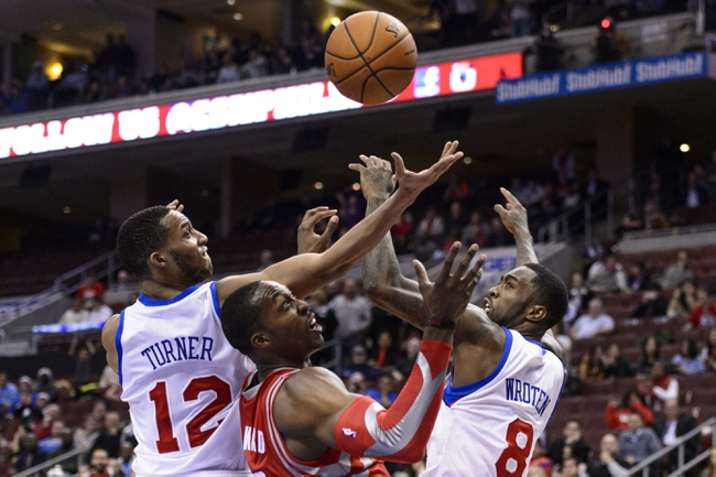 Nov 13, 2013; Philadelphia, PA, USA; Houston Rockets forward Dwight Howard (12) battles for a rebound with Philadelphia 76ers guard Evan Turner (12) and guard Tony Wroten (8) during the fourth quarter at Wells Fargo Center. The Sixers defeated the Rockets 123-117. Mandatory Credit: Howard Smith-USA TODAY Sports