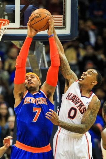 Nov 13, 2013; Atlanta, GA, USA; New York Knicks small forward Carmelo Anthony (7) grabs a pass in front of Atlanta Hawks point guard Jeff Teague (0) in the second half at Philips Arena. The Knicks won 95-91. Mandatory Credit: Daniel Shirey-USA TODAY Sports