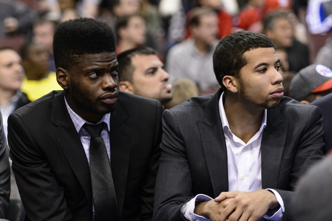 Nov 13, 2013; Philadelphia, PA, USA; Philadelphia 76ers center Nerlens Noel (4) and guard Michael Carter-Williams (1) (L to R) watch from the bench during the fourth quarter against the Houston Rockets at Wells Fargo Center. The Sixers defeated the Rockets 123-117. Mandatory Credit: Howard Smith-USA TODAY Sports