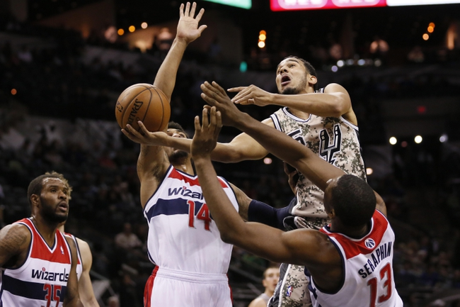 Nov 13, 2013; San Antonio, TX, USA; San Antonio Spurs guard Cory Joseph (top) goes in for a basket but draws the offensive foul against Washington Wizards center Kevin Seraphin (13) during the second half at AT&T Center. The Spurs won 92-79. Mandatory Credit: Soobum Im-USA TODAY Sports
