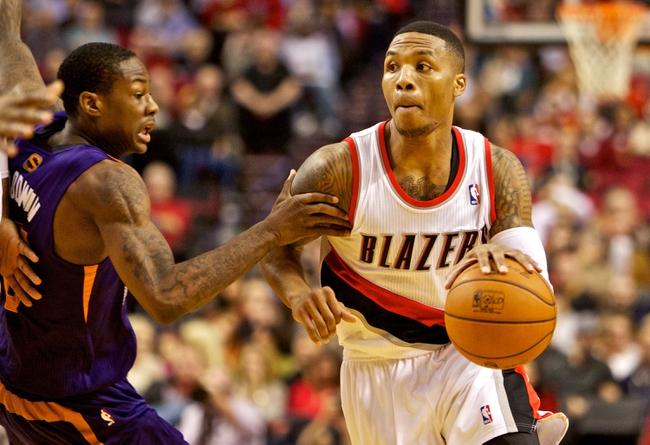 Nov 13, 2013; Portland, OR, USA; Portland Trail Blazers point guard Damian Lillard (0) drives past Phoenix Suns shooting guard Archie Goodwin (20) at the Moda Center. Mandatory Credit: Craig Mitchelldyer-USA TODAY Sports