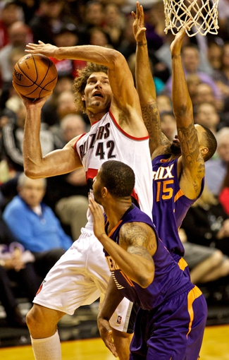 Nov 13, 2013; Portland, OR, USA; Portland Trail Blazers center Robin Lopez (42) shoots over Phoenix Suns power forward Markieff Morris (11) at the Moda Center. Mandatory Credit: Craig Mitchelldyer-USA TODAY Sports