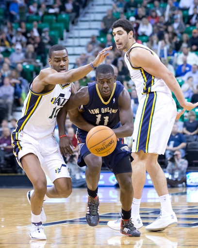 Nov 13, 2013; Salt Lake City, UT, USA; New Orleans Pelicans point guard Jrue Holiday (11) dribbles between Utah Jazz point guard Alec Burks (10) and center Enes Kanter (0) during the second half at EnergySolutions Arena. The Jazz won 111-105. Mandatory Credit: Russ Isabella-USA TODAY Sports