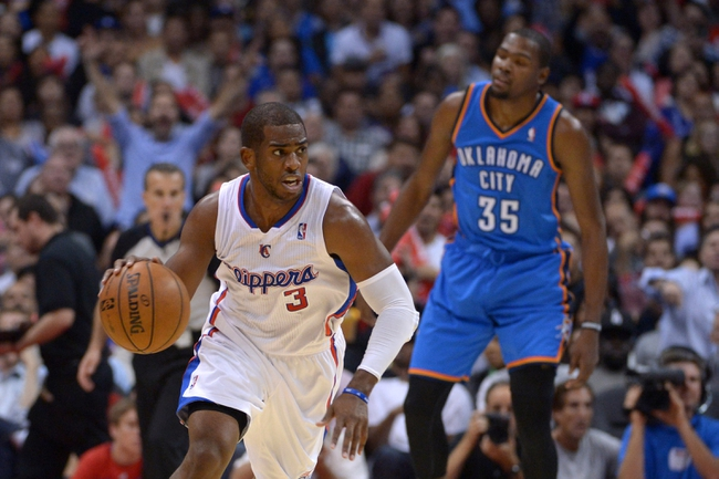 Nov 13, 2013; Los Angeles, CA, USA; Los Angeles Clippers guard Chris Paul (3) dribbles the ball with Oklahoma City Thunder forward Kevin Durant (35) in pursuit at Staples Center. The Clippers defeated the Thunder 111-103. Mandatory Credit: Kirby Lee-USA TODAY Sports