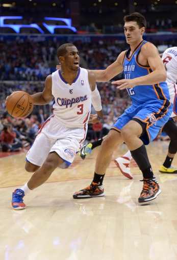 Nov 13, 2013; Los Angeles, CA, USA; Los Angeles Clippers guard Chris Paul (3) is defended by Oklahoma City Thunder center Steven Adams (12) at Staples Center. The Clippers defeated the Thunder 111-103. Mandatory Credit: Kirby Lee-USA TODAY Sports