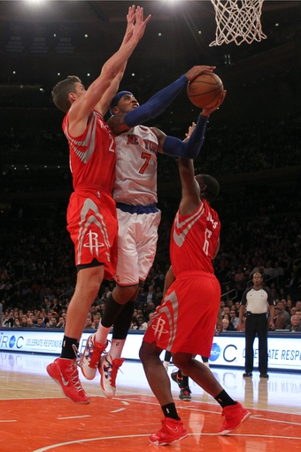 Nov 14, 2013; New York, NY, USA; New York Knicks small forward Carmelo Anthony (7) shoots over Houston Rockets small forward Chandler Parsons (25) and Houston Rockets power forward Terrence Jones (6) during the fourth quarter of a game at Madison Square Garden. The Rockets beat the Knicks 109-106. Mandatory Credit: Brad Penner-USA TODAY Sports