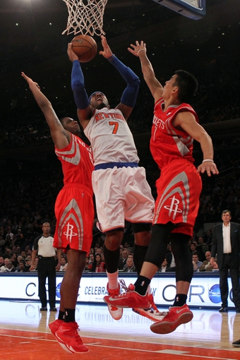 Nov 14, 2013; New York, NY, USA; New York Knicks small forward Carmelo Anthony (7) shoots over Houston Rockets power forward Terrence Jones (6) and Rockets point guard Jeremy Lin (7) during the fourth quarter of a game at Madison Square Garden. The Rockets beat the Knicks 109-106. Mandatory Credit: Brad Penner-USA TODAY Sports