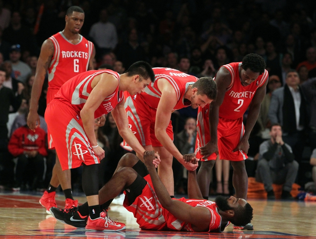 Nov 14, 2013; New York, NY, USA; Houston Rockets shooting guard James Harden (13) is helped up by teammates point guard Jeremy Lin (7) and small forward Chandler Parsons (25) and point guard Patrick Beverley (2) during the fourth quarter of a game at Madison Square Garden. The Rockets beat the Knicks 109-106. Mandatory Credit: Brad Penner-USA TODAY Sports