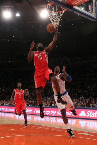 Nov 14, 2013; New York, NY, USA; Houston Rockets shooting guard James Harden (13) drives to the basket on New York Knicks shooting guard Iman Shumpert (21) during the second quarter of a game at Madison Square Garden. Mandatory Credit: Brad Penner-USA TODAY Sports